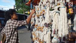 Pedagang merapikan pelita dagangannya yang dijual di Jalan Sam Ratulangi, Kota Gorontalo, Rabu (22/5/2019). Pelita ini terbuat dari botol bekas yang dipasangi sumbu. (Liputan6.com/Arfandi Ibrahim)