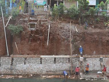 Pekerja membangun turap di bantaran Kali Cijantung, Jakarta Timur, Kamis (11/10). Pembangunan turap bertujuan mencegah longsor yang dapat membahayakan warga sekitar. (Liputan6.com/Immanuel Antonius)