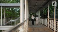 Pejalan kaki melintasi JPO yang merupakan akses menuju Halte Transjakarta CSW di kawasan Kebayoran Baru, Jakarta Selatan, Rabu (30/10/2019). JPO yang tak kunjung dipasang lift dan eskalator tersebut dibangun untuk menunjang koridor 13 Transjakarta. (Liputan6.com/Immanuel Antonius)