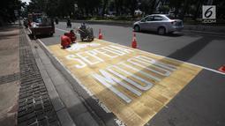 Pekerja menyelesaikan pengecatan rambu jalur kuning khusus sepeda motor di Jalan Medan Merdeka, Jakarta, Selasa (16/1).  Nantinya, pemotor hanya boleh melintas kawasan ini melalui jalur mengikuti jalan bercat kuning tersebut. (Liputan6.com/Arya Manggala)