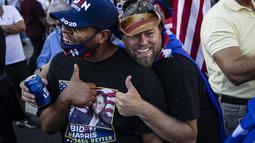 Seorang pendukung Presiden Donald Trump (kiri) dan seorang pendukung mantan Wakil Presiden Joe Biden (kanan) berpelukan saat yang lain merayakan hasil Pilpres Amerika Serikat di Black Lives Matter Plaza, dekat Gedung Putih di Washington pada Minggu (8/11/2020). (Samuel Corum/Getty Images/AFP)