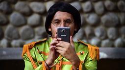 Seorang peserta mengambil gambar saat kegiatan untuk memecahkan rekor dunia dengan jumlah terbesar orang mengenakan pakaian dan bergaya seperti  The Beatles di sebuah taman di Mexico City, Meksiko 28 November 2015. (AFP PHOTO/ALFREDO ESTRELLA)