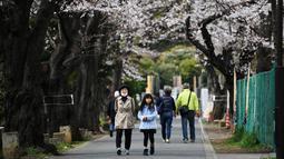 Sejumlah warga berjalan di bawah pohon sakura yang sedang mekar bunganya di distrik Taito, Tokyo, Jepang (26/3). Pohon sakura berbunga setiap satu tahun sekali, kuncup bunga sakura mulai terlihat di akhir musim dingin pada bulan Maret. (AFP Photo/Charly Triballeua)