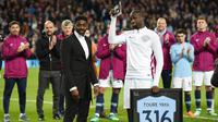 Gelandang Manchester City, Yaya Toure, mendapatkan penghargaan saat perpisahan di Stadion Etihad, Rabu (9/5/2018). Laga tersebut menjadi ajang perpisahan sang pemain bersama The Citizens. (AFP/Oli Scarff)