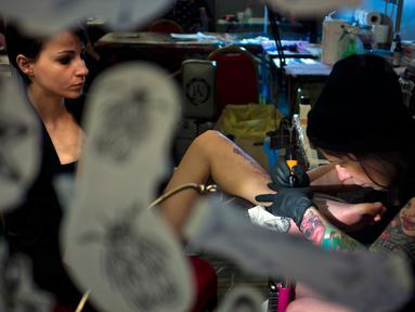 Seniman tato wanita, Andrada Vasili membuatkan tato pada pelanggannya selama Konvensi Tato Internasional bertema 'Sisi Lain dari Tinta' di ibu kota Italia, Roma, 11 Maret 2017. (AP Photo/Domenico Stinellis)