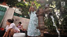 Warga menggunakan pompa air manual saat mencuci pakaian di pinggir jalan kawasan Kramat Pulo, Senen, Jakarta, Kamis (27/12). Para ibu ini mengaku harus bayar jika ingin buang air di WC umum yang berada di pemukiman. (Merdeka.com/Iqbal S. Nugroho)