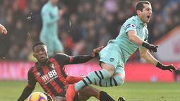 Gelandang Arsenal Henrikh Mkhitaryan saat dijegal Jeferrson Lerma pada laga lanjutan Premier League yang berlangsung di stadion Dean Court, Inggris, Minggu (25/11).  Arsenal menang 2-1. (AFP/Glyn Kirk)