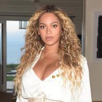 Foto tersebut tampak elegan dengan latar belakang bunga-bunga yang beraneka warna. Ia juga mengenakan selendang berwarna biru yang disangkutkan pada bagian belakang  di kepalanya. (Instagram/Beyonce)