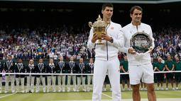 Juara Wimbledon 2015, Novak Djokovic dan Runner up, Roger Federer berpose bersama piala mereka usai final tunggal putra Wimbledon 2015, London, Minggu (12/7). Ini adalah gelar Wimbledon ketiga bagi Djokovic.  (REUTERS/Stefan Wermuth)