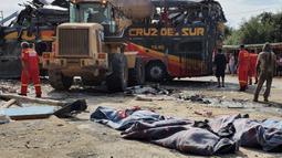 Petugas dibantu penduduk setempat mengevakuasi korban bus tingkat setelah menabrak mobil-mobil yang diparkir di daerah Arequipa, Peru, Senin (6/1/2020). Sebelum kecelakaan, bus itu berangkat dari Kota Lima menuju Arequipa. (Photo by Javier Casimiro / AFP)