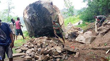 Longsor batu besar tutup jalan, warga dan Babinsa gotong royong membuka akses jalan setapak dan pindahkan batu berukuran lebih kecil. (Liputan6.com/ Dionisius Wilibardus)