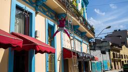 Seorang pria mengecat bagian balkon di Havana, Kuba (28/12). Kota ini terletak sekitar 144 kilometer di selatan-barat daya dari Key West, Florida.  (AP Photo / Desmond Boylan)
