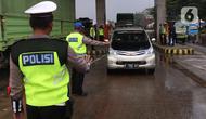 Petugas memberhentikan sebuah mobil saat penyekatan larangan mudik lebaran di gerbang tol Cikupa, Kabupaten Tangerang, Banten, Kamis (6/5/2021). Penyekatan dilakukan seiring telah diberlakukan larangan mudik Lebaran mulai dari 6 hingga 17 Mei 2021.  (Liputan6.com/Angga Yuniar)