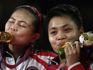 Atlet Badminton Ganda Putri Indonesia Apriyani Rahayu (kanan) dan Greysia Polii berpose dengan medali emas Olimpiade Tokyo 2020 di Musashino Forest Sports Plaza, Tokyo, Senin (2/8/2021). (Foto: AFP/Alexander Nemenov)