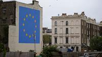 Mural pria tengah menghancurkan salah satu dari 12 bintang kuning bendera Uni Eropa di dinding kawasan Dover, Inggris, Senin (8/5). Bintang kuning itu merupakan simbol kesatuan, solidaritas dan harmoni di antara warga Eropa. (DANIEL LEAL-OLIVAS/AFP)