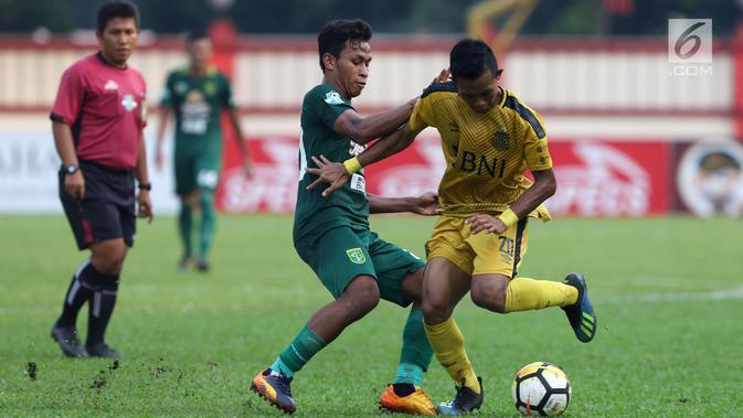 Pemain Bhayangkara FC, Sani Rizki Fauzi (kanan) berebut bola dengan pemain Persebaya pada lanjutan Go-Jek Liga 1 Indonesia bersama Bukalapak di Lapangan PTIK, Jakarta, Rabu (11/7). Babak pertama, Bhayangkara FC unggul 2-1. (Liputan6.com/Helmi Fthriansyah)