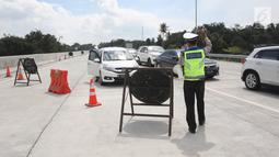 Petugas mengalihkan kendaraan pemudik di ruas Tol Salatiga-Kartasura, Barukan, Kabupaten Semarang, Jateng, Selasa (12/6). Pengalihan dilakukan bagi kendaraan yang menuju Solo untuk keluar di exit tol Tingkir Salatiga. (Liputan6.com/Arya Manggala)