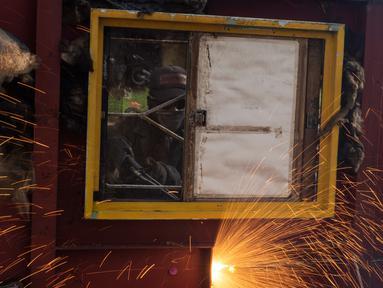Pekerja memotong kapal tua di Cilincing, Jakarta, Kamis (13/2/2020). Proses daur ulang ini dilakukan dengan cara memotong kapal menjadi bagian-bagian kecil yang kemudian dijual sebagai besi tua. (Xinhua/Agung Kuncahya B.)