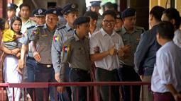 Wartawan Reuters, Wa Lone (tengah) dikawal oleh polisi setibanya di pengadilan distrik Yangon, Myanmar, Senin (3/9). Dua jurnalis Reuters dituduh melanggar undang-undang rahasia negara saat menyelidiki kekerasan terhadap Rohingya. (AP/Thein Zaw)