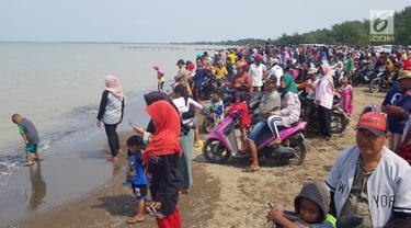 Warga berkerumun menantikan evakuasi pesawat Lion Air JT 610 di Pantai Pakis Jaya, Karawang, Jawa Barat, Senin (29/10). Warga yang penasaran berduyun-duyun datang ke pantai dekat lokasi jatuhnya pesawat. (Liputan6.com/Herman Zakharia)