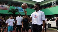 Pemain NBA dari Boston Celtics, Jaylen Brown menunjukkan kemampuannya memutar bola basket dengan satu jari saat memberi coaching clinics untuk siswa-siswi di SMAN 82 Jakarta, Kamis (26/7). (Liputan6.com/Arya Manggala)