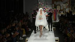 Gigi Hadid berjalan di runway mengenakan gaun rumah mode Moschino untuk koleksi SS19 selama gelaran fashion week di Milan, Italia, Kamis (20/9). Bagian kaki jenjang Gigi Hadid ditopang sepatu model pointed heels silver metalik. (AFP/Marco BERTORELLO)