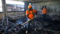 Seorang pekerja perlindungan sipil menyekop puing-puing hangus dari dalam Panti Asuhan Church of Bible Understanding tempat kebakaran terjadi, menewaskan 13 anak-anak di Kenscoff, di pinggiran Port-au-Prince, Haiti [Source: Dieu Nalio Chery / AP Foto]