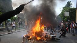 Pelajar membakar sepeda motor dan rambu lalu lintas saat berdemonstrasi di belakang Gedung DPR, Palmerah, Jakarta, Rabu (25/9/2019). Polisi masih melakukan pemeriksaan terhadap sejumlah pelajar yang berhasil diamankan. (Liputan6.com/Angga Yuniar)