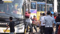 Penumpang turun dari bus Antar Kota Antar Provinsi (AKAP) di Terminal Kampung Rambutan, Jakarta, Selasa (19/6). Terdapat 691 bus kedatangan hingga siang ini. (Liputan6.com/Faizal Fanani)