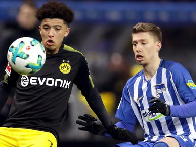 Pemain Borussia Dortmund, Jadon Sancho berebut bola dengan pemain Hertha Berlin, Mitchell Weiser dalam lanjutan Bundesliga di Olympiastadion Berlin, Sabtu (20/1). Borussia Dortmund hanya mampu bermain imbang 1-1 melawan Hertha Berlin. (AP/Michael Sohn)