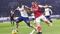 Pemain Tottenham Hotspur, Serge Aurier, berebut bola dengan pemain Arsenal, Granit Xhaka, pada laga Liga Inggris di London, Minggu (6/12/2020). Tottenham menang dengan skor 2-0. (Glyn Kirk/Pool via AP)