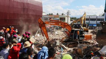 Eskavator membantu mengangkat puing bangunan yang runtuh akibat gempa di Pasar Meureudu, Pidie Jaya, Aceh, Kamis (8/12). Dikabarkan korban meninggal sudah mencapai 102 orang. (Liputan6.com/Angga Yuniar)