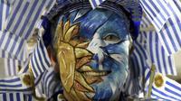 Salah satu pendukung timnas Uruguay mewarnai wajahnya dengan bendera negaranya saat mendukung timnya melawan Argentina pada laga kualifikasi Piala Dunia 2018 di Montevideo, Uruguay, (31/8/2017). Argentina imbang 0-0 lawan uruguay. (AP/Matilde Campodonico)