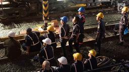 Petugas melihat proses evakuasi gerbongKRL Commuter Line dengan nomor KA 1722 jurusan Jatinegara - Bogor di kawasan Kebon Pedes, Bogor, Jabar Minggu (10/3). Proses evakuasi menggunakan crane dari Bandung. (Liputan6.com/Immanuel Antonius)