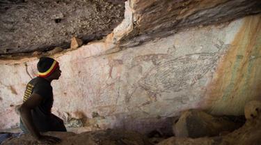 Foto dokumentasi yang diabadikan pada 15 Juli 2016 ini menunjukkan seorang penduduk asli mengamati lukisan batu yang menampilkan kanguru di wilayah Kimberley, Australia. (Xinhua/Peter Veth)