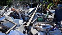 Seorang pria menyelamatkan barang berharga dari puing rumah yang rusak di Menggala, Lombok Utara, Rabu (8/8). Warga terdampak gempa Lombok mulai mengamankan barang berharga miliknya karena kuatir dijarah pihak tidak bertanggung jawab. (AFP/ADEK BERRY)