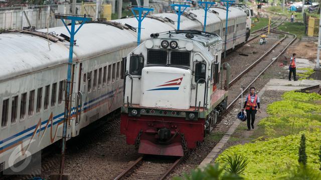 Petugas berjalan disamping kereta api di Stasiun Tanjung Priok, Jakarta Utara, Kamis (6/4). Acara HUT tersebut diselenggarakan oleh  PT Kereta Api Indonesia (KAI) Daop 1 bersama dengan Komunitas Pecinta Kereta Api Indonesia. (Liputan6.com/Gempur M. Surya)