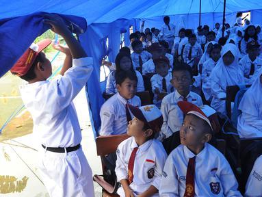 Murid-murid berada di dalam tenda darurat  akibat bangunan atau kelas roboh saat hujan deras  pada hari Rabu (1/1/2020) lalu di SDN Cirimekar 2, Cibinong, Bogor, Senin (6/1/2020). (merdeka.com/Arie Basuki)