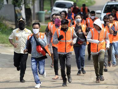 Warga pelanggar PSBB dihukum berlari saat terjaring Operasi Yustisi yang digelar petugas gabungan di BSD, Tangerang Selatan, Banten, Rabu (16/9/2020). Sanksi sosial lari sejauh 800 meter diberikan kepada warga pelanggar PSBB untuk memberikan efek jera. (merdeka.com/Dwi Narwoko)