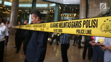 Garis polisi dipasang di pintu masuk Tower II Bursa Efek Indonesia (BEI), Jakarta, tempat ambruknya selasar lantai 1, Senin (15/1). Polisi belum membolehkan awak media dan yang lain untuk memasuki gedung tersebut. (Liputan6.com/Johan Tallo)