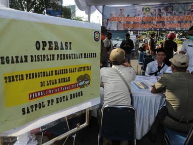 Petugas gabungan mendata warga yang tidak mengenakan masker saat Operasi Masker Gabungan di Perempatan Ciawi, Bogor, Kamis (10/9/2020). Razia masker yang dilakukan Pemkot dan Pemkab Bogor ini menyasar warga yang tidak mengenakan masker dengan denda sebesar Rp 100.000. (merdeka.com/Arie Basuki)