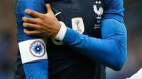 Penyerang timnas Prancis dan PSG, Kylian Mbappe memegangi bahunya dalam laga uji coba melawan timnas Uruguay di Stade de France, Rabu (21/11). Mbappe mendarat dengan tidak sempurna saat beradu dengan kiper lawan Martin Campana. (AP/Christophe Ena)