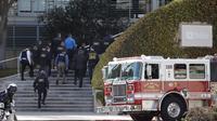 Petugas penegak hukum berjalan masuk ke dalam kantor pusat YouTube usai insiden penembakan di San Bruno, California, Amerika Selatan, Selasa (3/4). Polisi mengatakan tersangka yang identitasnya belum diketahui itu dilengkapi dengan pistol.  (AP/Jeff Chiu)