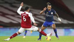 Pemain Arsenal, Gabriel, berusaha menghadang penyerang Southampton, Theo Walcott, pada laga Liga Inggris di Stadion Emirates, Kamis (17/12/2020). Kedua tim bermain imbang 1-1. (Peter Cziborra/Pool via AP)