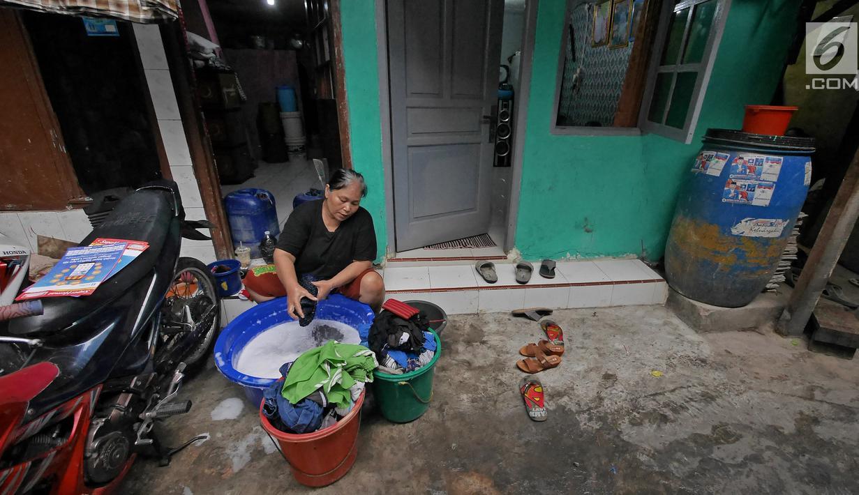 Warga mencuci pakaian di depan rumahnya di Kawasan Muara Baru, Jakarta, Selasa (9/7/2019). Pada saat musim kemarau air sumur tidak mengalir deras, untuk memenuhi air bersih warga dalam sehari mengeluarkan uang Rp. 15.000 untuk membeli enam derigen untuk air bersih. (Liputan6.com/Herman Zakharia)