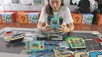 Pengunjung bermain game bot di acara bertajukThe 90s Festival, Jakarta, Sabtu (25/11). Dalam event tersebut terdapat berbagai jenis game, pernak-pernik, makanan, atribut, tokoh super hero, barang-barang generasi tahun 90an. (Liputan6.com/Herman Zakharia)