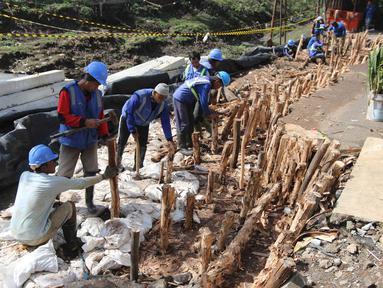 Petugas Sudin Sumber Daya Air Jakarta Timur melakukan perbaikan jalan ambles di Jalan Al-Mujahidin, Cipinang, Pulogadung, Jakarta Timur, Rabu (21/2). Jalan tersebut ambles sepanjang 30 meter dan kedalaman 1,5 meter. (Liputan6.com/Arya Manggala)