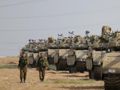 Tentara Israel berjalan melewati tank di dekat perbatasan Gaza-Israel, Jumat (19/10). Sekitar 60 tank dan kendaraan lapis baja pengangkut personel bergerak melalui jalan-jalan Israel menuju perbatasan Gaza. (AP Photo/Ariel Schalit)