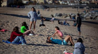Orang-orang bersantai di pantai di Badalona, dekat Barcelona, Spanyol, Selasa, (28/4/2020). Lockdown untuk memerangi penyebaran virus corona terus berlanjut di Spanyol. (AP Photo/Emilio Morenatti)