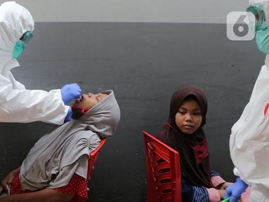 "Petugas Kesehatan mengambil sampel lender saat Swab Test COVID 19 yang digelar secara ""door to door"" bagi warga pendatang di Kawasan kampung Tengah, Kramat Jati, Jakarta, Jumat (12/6/2020). Tes Swab dengan mendatangi rumah itu untuk mencegah penyebaran pandemi Covid-19. (merdeka.com/Imam Buhori)"